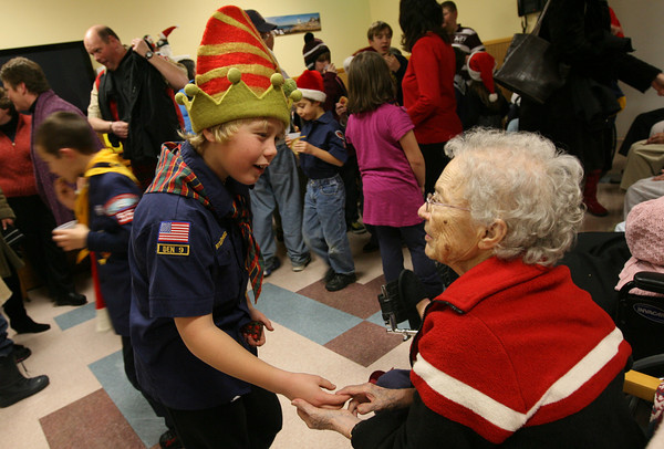 Rockport: Eamon Wheeler, a member of Rockport Cub Scout Pack 55, speaks with Emily Hanrahan after the scouts sang Christmas carols at Den-Mar Rehab and Nursing Center on Wednesday night. Hanrahan was telling him about when she was a girl scout leader. Photo by Kate Glass/Gloucester Daily Times