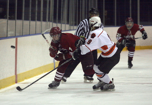 Salem: Gloucester's Ben Favazza knocks the puck past Beverly's Matt Hamor their season opener at Rockett Arena last night. The Fishermen lost 3-2. Photo by Kate Glass/Gloucester Daily Times