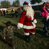 Manchester: Santa holds the hand of Christian Gauthier, 5, of Salem after Santa arrives to the Manchester Athletic Club by helicopter Saturday afternoon. Mary Muckenhoupt/Gloucester Daily Times