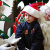 Essex: Brian Kelly, 4, chats with Mrs. Claus while sitting on Sant's lap during Breakfast with Santa at Essex Elementary School Saturday morning. On on the things Brian has asked for for Christmas is an iPad. Mary Muckenhoupt/Gloucester Daily Times