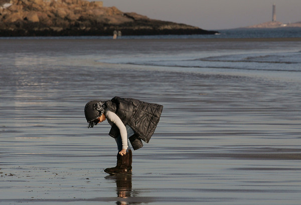 Gloucester: Eve Poliskey of Glocuester puts her boots back on after walking barefoot at Good Harbor Beach with her dogs Friday afternoon. Mary Muckenhoupt/Gloucester Daily Times