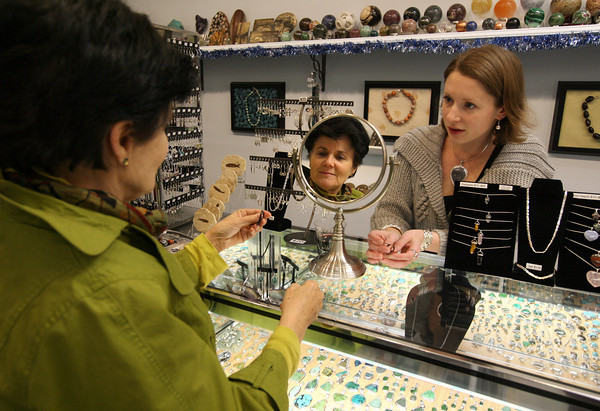 Gloucester: Vanessa Parsons of the Village Silversmith helps Norma Hardy select a pair of earrings during Ladies Night in Gloucester yesterday. Many stores downtown offered food, drinks, and discounts on merchandise to entice people to shop locally. Photo by Kate Glass/Gloucester Daily Times