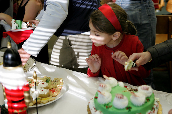 Essex: Sophie Quine, 6, carefully decides which yummy Christmas cookie to choose during the Nutcracker Party held at the TOHP Burnham Library in Essex Saturday afternoon.  Mary Muckenhoupt/Gloucester Daily Times