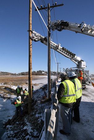 Gloucester: National Grid employees install a new utility pole along Thatcher Road in Gloucester, which will support one that snapped and fell across the road during the recent snowstorm. Photo by Kate Glass/Gloucester Daily Times
