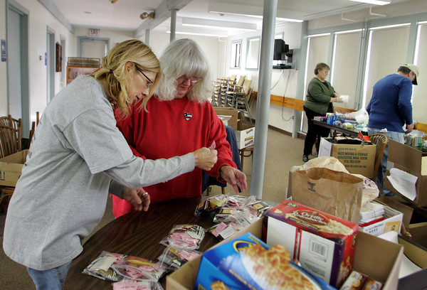 Gloucester: Cher Sheckler, left, and Judy Hickory put together bags of tea, instand coffee, and sugar packets to go inside the care packages that are being sent over to local troops at the Veteran's Service's Center on Emerson Avenue Monday morning.  Sheckler helped pack the box that will being going over to her son Adam Taschler who is currently serviing a 14 month deployment. Mary Muckenhoupt/Gloucester Daily Times