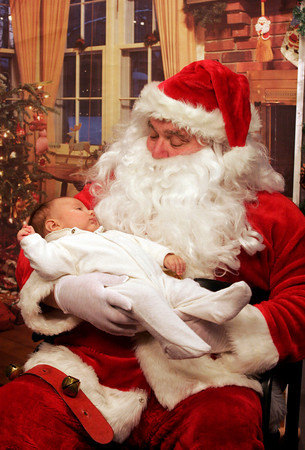 """Gloucester: Thomas Merchant, 3 months, relaxes in Santa's arms during a taping of """"Santa Party!"""" at the Cape Ann TV Studio. """"Santa Party!"""" will air from 5:30 to 9:30 p.m. on Christmas Eve and from 6 a.m. to 1 p.m. and 5:30 to 9:00 p.m. on Christmas Day. Photo by Kate Glass/Gloucester Daily Times"""