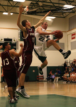 Manchester: Manchester Essex's Joe Mussachia leaps around Rockport's Dan Gray last night. Photo by Kate Glass/Gloucester Daily Times
