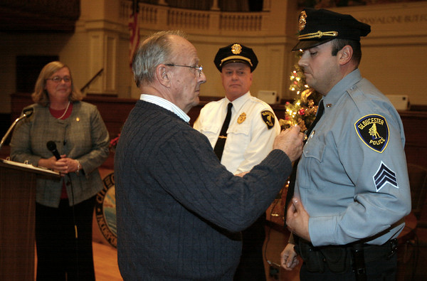 Gloucester: Ken Gossom pins a new badge on his son, Michael Gossom, who was recently promoted to Police Sergeant, as Mayor Carolyn Kirk and Police Chief Michael Lane look on during the Public Safety Badge Ceremony at City Hall on Thursday. Photo by Kate Glass/Gloucester Daily Times