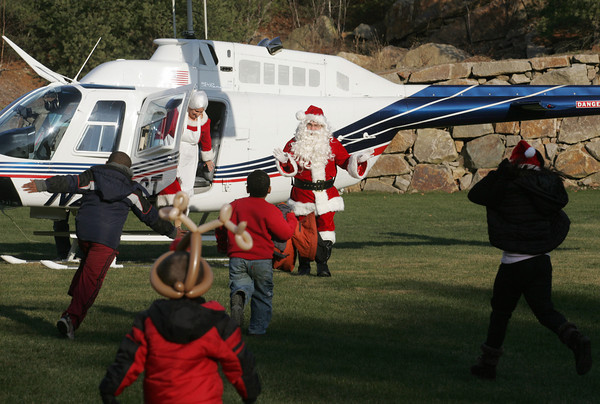 Manchester: Kids run over as Santa and Mrs. Claus arrive from the North Pole to the Manchester Athletic Club by helicopter Saturday afternoon. Mary Muckenhoupt/Gloucester Daily Times