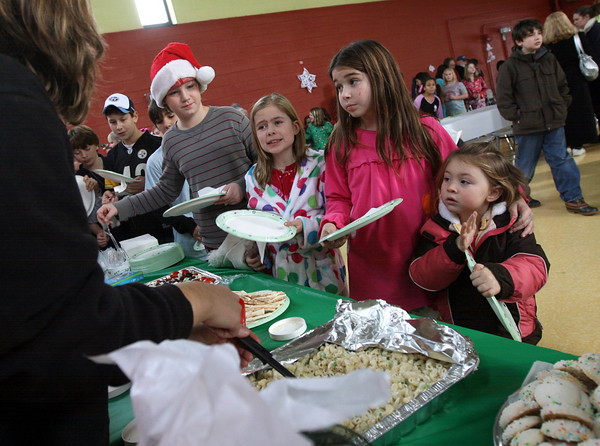Gloucester: From right: Abigail Corbett, 3, Emma Allen, 9, and Ella Kulak, 9, try to decide what food they want during a party at the Gloucester Community Arts Charter School on Thursday. Photo by Kate Glass/Gloucester Daily Times