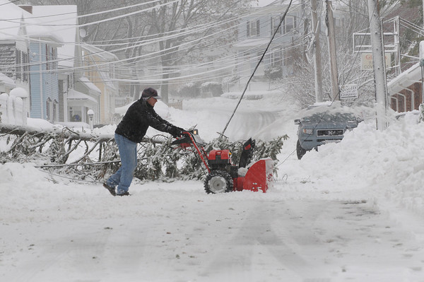 Gloucester: Gabe Onorio clears the snow from his driveway,as he waits for crews to remove a fallen tree that ripped down the powerline that goes to his home on Whittemore st Monday morning. Despite the meter box nearly being torn from the house, he still had power. Desi Smith/Gloucester Daily Times. December 27,3010.