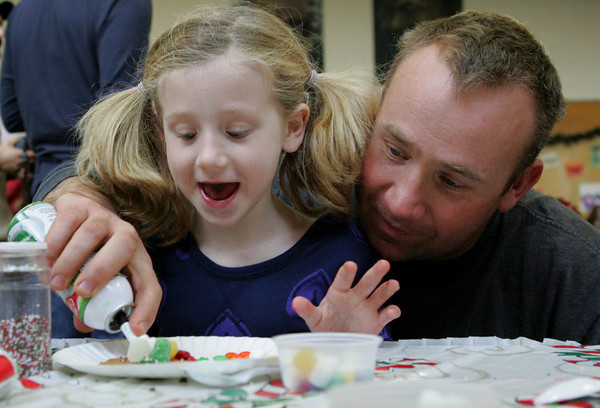 Essex: Riley Huber, 5, likes how much frosting her dad, Keith, is putting on her gingerbread cookie during Breakfast with Sanata at Essex Elementary School Saturday morning. Mary Muckenhoupt/Gloucester Daily Times