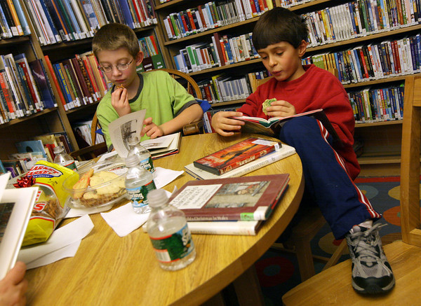 """Manchester: Will Russo, left, and William Pollock snack on sugar cookies and pretzels while reading """"A Child's Christmas in Wales"""" during the Ramblin' Readers program at the Manchester Public Library on Thursday. The group also read from """"The Diamond Tree: Jewish Tales from Around the World."""" Photo by Kate Glass/Gloucester Daily Times"""