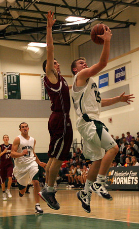 Manchester: Manchester Essex's Alex Carr tries to shoot around Rockport's Andrew Visnick last night. Photo by Kate Glass/Gloucester Daily Times