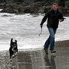 Rockport: Pavel Korzinek and his dog, Pepik, run away from a wave while playing fetch on Front Beach yesterday afternoon. Photo by Kate Glass/Gloucester Daily Times