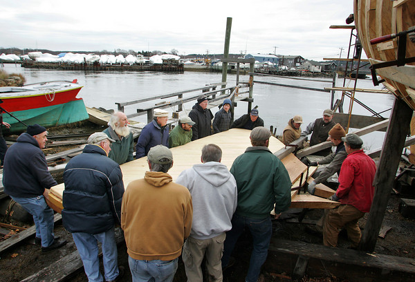 Essex: 15 men help Harold Burnham, right, carry a frame with a bulkhead attached as far as they can make it as the framing process of the schooner Pinky Ardelle is almost complete at H.A. Burnhams Boat Building and Design Saturday afternoon.  Despite all the man power this frame was too heavy to hoist into place without the help of a fork lift that could be used when the ground becomes less muddy. Mary Muckenhoupt/Gloucester Daily Times