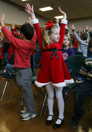 Essex: Riley Huber raises her arms as the kids at Essex Elementary School play Simon Says in between acts during their holiday performance on Thursday. Photo by Kate Glass/Gloucester Daily Times