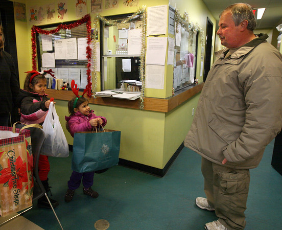 Gloucester: Makayla Mateo, 6, and Kiara Olson, 3, deliver items collected by the O'Maley Middle School Student Council to Jim Noble, Shelter Manager of Action, Inc., yesterday. Students collected toothbrushes, toothpaste, shampoo, soap, deodorant and razor blades for the shelter. Photo by Kate Glass/Gloucester Daily Times