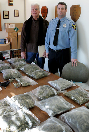 Gloucester: Detective Kenny Ryan and patrolman Brian Aiello stand with ten pounds of confescated marijuana at the Gloucester Police Department Friday monring.  Five pounds were confiscated in early Decmeber and the other 5 pounds were confiscated Wednesday from two men from Vermont who brought the marijuana to Gloucester. Mary Muckenhoupt/Gloucester Daily Times