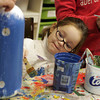 Gloucester: Jessica Cote, 4, works at painting her buoy blue as her dad helps keep the buoy steady at Art Haven Saturday afternoon. The buoys were hung on the lobster trap tree for the tree lighting which took place Saturday night. Mary Muckenhoupt/Gloucester Daily Times