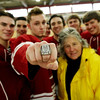ALLEGRA BOVERMAN/Staff photo. Gloucester Daily Times. Gloucester: Kathy Milbury of Rockport brought her brother Michael MIlbury's Stanley Cup ring to the Gloucester high school varsity boys hockey team practice on Tuesday. Wearing the ring at center is co-captain Vincenzo Terranova, with Kathy Milbury next to him at right. Seniors from the team are gathered with them.