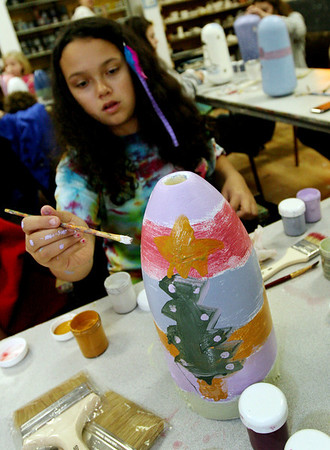 ALLEGRA BOVERMAN/Staff photo. Gloucester Daily Times. Gloucester: Kaleigh Tobin, 10, paints a buoy at Art Haven on Friday afternoon. Organizers said there were about 66 children in the first hour working on decorated buoys to be hung on the Lobster Trap tree on Saturday before it will be lit.