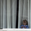 ALLEGRA BOVERMAN/Staff photo. Gloucester Daily Times. Hayden Koller, 2, of Gloucester, plays in the window of her grandmother, Dawn Koller's dance studio, Dawn's Studio of Dance, in Gloucester on Tuesday afternoon.