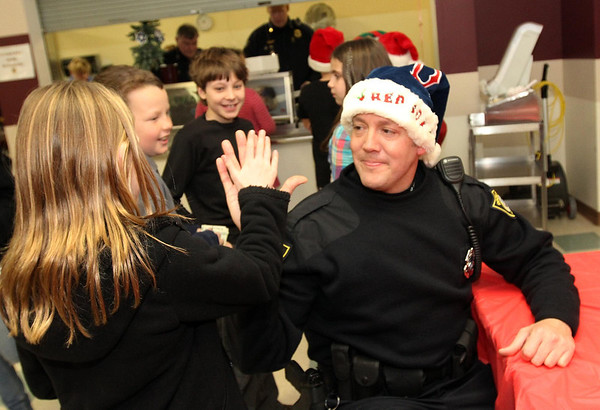 Courtesy photo/Gloucester Daily Times. Rockport: Members of the Rockport Police Department served lunch to Rockport Elementary School students on Friday. The school and police department have been planning to do this for a while and hope to make it a new tradition. Patrolman Dan Mahoney, right, greets fourth grader Samantha Budrow.