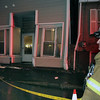 ALLEGRA BOVERMAN/Staff photo. Gloucester Daily Times. Gloucester: Gloucester Firefighter Tony Trupiano and other fire department personnel were on the scene at 75 Washington St. on Wednesday evening. A woman driving a Suburban, according to  fire department personnel, drove up on the curb and then struck 75 Washington Street on Wednesday evening, affecting the building's structure where seven people live, and nicking but not seriously damaging the building next door, No. 73. No one was hurt and firefighters were awaiting the building inspector's advice on whether to allow residents back inside.
