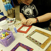 "ALLEGRA BOVERMAN/Staff photo. Gloucester Daily Times. Gloucester:  Micaela O'Connor, 17, designs her own picture frames at Art Haven's ""Picture Perfect"" winter workshop on Monday afternoon. She and other participants took photos of each other in the digital studio and printed them to place in the frames. The center has several more workshops planned this week, including a wrapping paper (design your own wrapping paper design) project workshop on Wed., Dec. 21, reindeer games (board game making workshop) on Thurs., Dec. 22, and a Christmas Collaboration on Fri., Dec. 23, where participants will work together to make a large piece of art. All workshops are from 3:30 - 5:30 p.m. Call Art Haven to reserve a spot at 978-283-3888."