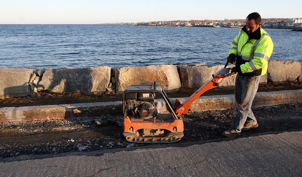 ALLEGRA BOVERMAN/Staff photo. Gloucester Daily Times.Rockport: Jon Miller of Miller Golf Construction of Beverly prepares the ground for asphalt for a new sidewalk and curb along Beach Street in Rockport on Tuesday afternoon. He was also patching the road and his company also rebuilt the seawall, which had been crumbling.