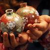 "ALLEGRA BOVERMAN/Staff photo. Gloucester Daily Times. Manchester: <br /> Sasa Willems, 10, shows off globe ornamants she made during an ornament making workshop at the Manchester Public Library on Thursday afternoon. About 10 children made two ornaments each using glitter, rhinestones, stickers and other shiny materials to make ""glistening, glittery globe ornaments."""