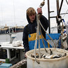 ALLEGRA BOVERMAN/Staff photo. Gloucester Daily Times. Gloucester: Peter Kammerer, 18, young lobsterman, loading bait onto a lobster boat.