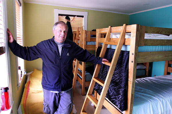 Jim Noble, Action's shelter manager, stands in a bedroom at the Action's Rogers Street location. Jesse Poole/Gloucester Daily Times Dec. 05, 2011