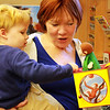 James Hughs, held by his grandmother, Margaret Hughs of Manchester, plays with a Curious George jack-in-the-box at the Manchester Public Library on Wednesday morning. Jesse Poole/Gloucester Daily Times Dec. 07, 2011