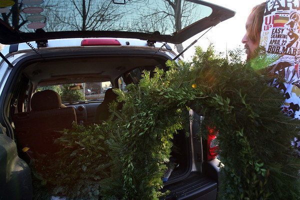 ALLEGRA BOVERMAN/Staff photo. Gloucester Daily Times. Rockport: Colin Phillips, an employee at Blue Gate Gardens in Rockport, loads five large wreaths into Rockport resident Charles Clark's vehicle on Friday afternoon. Clark was going to decorate his law office in Gloucester with the wreaths, which have boxwood worked into them. He also bought a boxwood planted in a decorative urn.