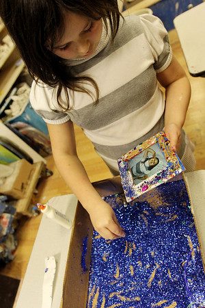 "ALLEGRA BOVERMAN/Staff photo. Gloucester Daily Times. Gloucester: Kaylee Allen, 8 1/2, sprinkles bright blue glitter on a picture frame she created at Art Haven's ""Picture Perfect"" winter workshop on Monday afternoon. The center has several more workshops planned this week, including a wrapping paper (design your own wrapping paper design) project workshop on Wed., Dec. 21, reindeer games (board game making workshop) on Thurs., Dec. 22, and a Christmas Collaboration on Fri., Dec. 23, where participants will work together to make a large piece of art. All workshops are from 3:30 - 5:30 p.m. Call Art Haven to reserve a spot at 978-283-3888."