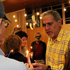 ALLEGRA BOVERMAN/Staff photo. Gloucester Daily Times. Gloucester: Dozens of menorahs were lit for the first night of Hanukkah during the community Hanukkah party held at Temple Ahavat Achim in Gloucester on Tuesday evening. Barry Pett, right, lights candles for people to light their own menorahs with during the festivities.