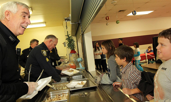 Courtesy photo/Gloucester Daily Times. Rockport: Members of the Rockport Police Department served lunch to Rockport Elementary School students on Friday. From left are: Patrolman Roger Lesch, Sgt. Bob Tibert, and in the background, Chief John McCarthy and Sgt. Mark Schmink. Patrolman Lesch talks with fourth grader Charlie Ruiter, far right. The school and police department had been planning this for a while, and hope to make it a tradition.