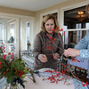 ALLEGRA BOVERMAN/Staff photo. Gloucester Daily Times. Rockport: Sue Andersen, left, and Tamsen Endicott cut winterberries to add to centerpieces for the sunporch of The Captain's House Inn in preparation or the Seashells and Jingle Bells Inn and Home Kitchen Tour of Rockport which will be held on December 10th from 1- 6 p.m.