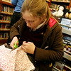 Caileigh Cunningham, 11, cuts out material to make doll clothing with during the Manchester Public Library's annual Gift Making and Wrapping workshop held on Thursday afternoon. There were more than 30 children busy making a variety of gifts - from dressed-up dolls and calendars to beaded jewelry and picture frames and more. Then they could wrap them.