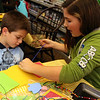 ALLEGRA BOVERMAN/Staff photo. Library volunteer Emily Stanton, 12, right, helps Matt Russo, 6, sew together pocket organizers during the Manchester Public Library's annual Gift Making and Wrapping workshop held on Thursday afternoon. There were more than 30 children busy making a variety of gifts - from dressed-up dolls and calendars to beaded jewelry and picture frames and more. Then they could wrap them.