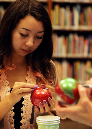 "ALLEGRA BOVERMAN/Staff photo. Gloucester Daily Times. Manchester: Tiffany Vander Laan, 16, works carefully on a globe ornamant during an ornament making workshop at the Manchester Public Library on Thursday afternoon. Young Adult librarian Anne Cowman works on hers at right. About 10 children made two ornaments each using glitter, rhinestones, stickers and other shiny materials to make ""glistening, glittery globe ornaments."""