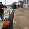 ALLEGRA BOVERMAN/Staff photographer. Gloucester Daily Times. Gloucester: Kevin Levesque of McGinnis Paving, Inc., of Beverly Farms, smoothes newly laid down asphalt along Webster Street on Tuesday afternoon to cover up work just done on gas lines below.