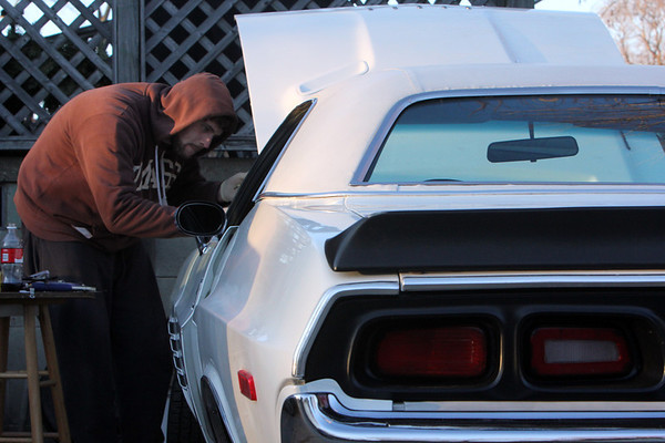 """ALLEGRA BOVERMAN/Staff photo. Gloucester Daily Times. Gloucester: Kyle Dutton of Lanesville works on his white 1973 Dodge Challenger on Tuesday afternoon. He is trying to fix an electrical problem at the moment. This car is """"my baby,"""" he said. Part of the reason he got the vehicle was so he could work on it. Some day he wants to build a car completely from scratch, he said."""