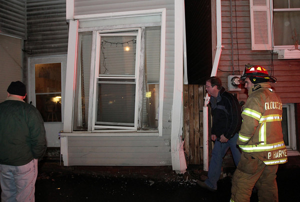 ALLEGRA BOVERMAN/Staff photo. Gloucester Daily Times. Gloucester: City Building Inspector Bill Sanborn, second from right, arrives at 75 Washington St. in Gloucester on Wednesday evening following an accident where a woman driving a Suburban went up on the curb and into the building, nicking the house next door at No. 73 and affecting the structure of No. 75, where about seven people live, and at least one pet. Sanborn was to determine if the building's structure was safe for residents to return to. With him is Gloucester Fire Capt. Phil Harvey at far right. No one was hurt and the driver refused treatment, Harvey said.