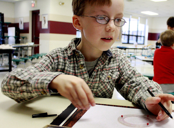 Eli Mueller, 8, has fun working on drawing geometric shapes at a parent-run math program hosted at Rockport Elementary School on Saturday morning. Jesse Poole/Gloucester Daily Times Dec. 15, 2011