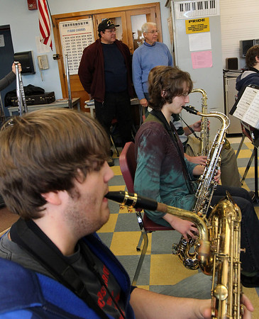 ALLEGRA BOVERMAN/Staff photo. Gloucester Daily Times. Gloucester: Gloucester High School senior Chris Taylor, bottom, plays a baritone saxophone during rehearsal of the jazz band Docksiders on Tuesday. A <br /> new baritone saxophone was just obtained by members of the former Atlantic Brassman Senior Drum & Bugle Corps, including Billy Goulart, left, and Gaspar LaFata, standing, background. The organization had money to use and wanted to help the music department.