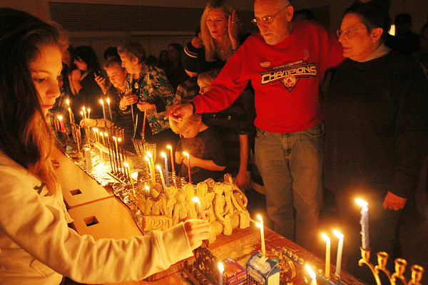 ALLEGRA BOVERMAN/Staff photo. Gloucester Daily Times. Gloucester: Dozens of menorahs were lit for the first night of Hanukkah during the community Hanukkah party held at Temple Ahavat Achim in Gloucester on Tuesday evening. At left is Molly Finch, 12, lighting a candle. At right is Jerry and Maxine Rosenberg.