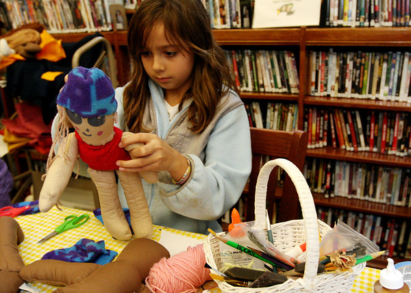 ALLEGRA BOVERMAN/Staff photo. Gloucester Daily Times. Manchester: Izzy Eliassen, 9, was making bright fleece clothing for a doll during the Manchester Public Library's annual Gift Making and Wrapping workshop held on Thursday afternoon. There were more than 30 children busy making a variety of gifts - from calendars to beaded jewelry and picture frames and more. Then they could wrap them.